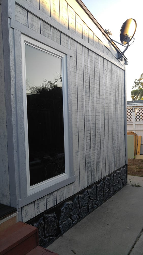 Exterior remodel with white siding and rock skirting