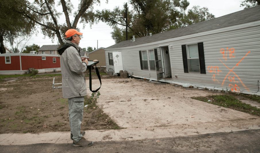 Mobile home inspector standing outside of mobile home with camera