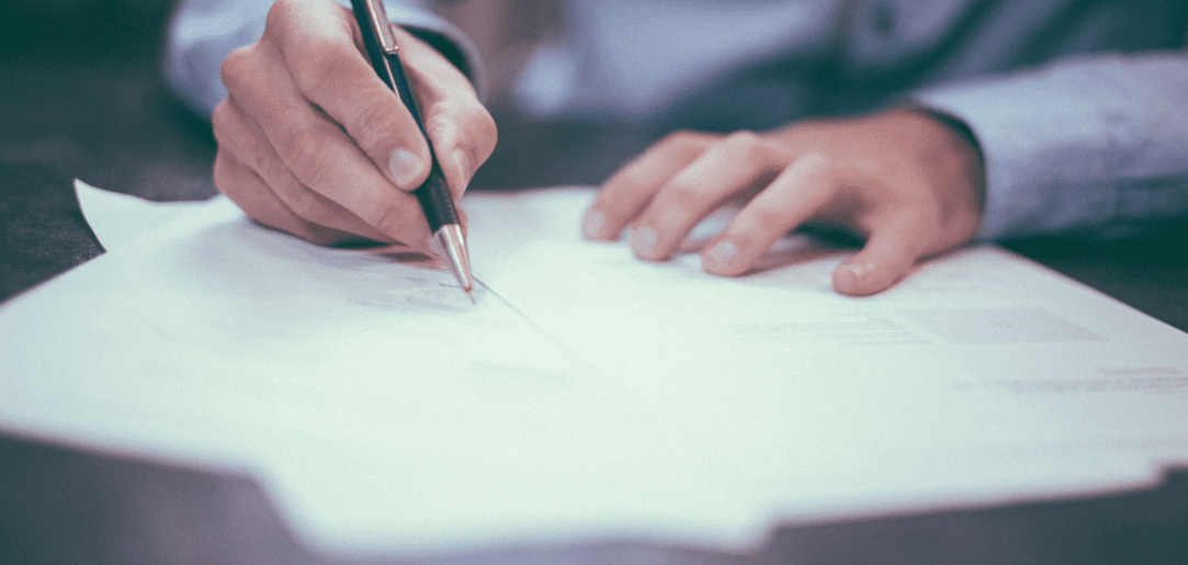 Man signing a document with pen in hand