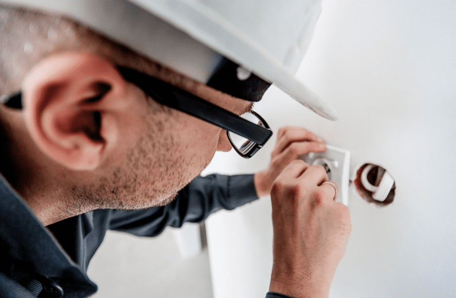 An electrician working on an electric outlet