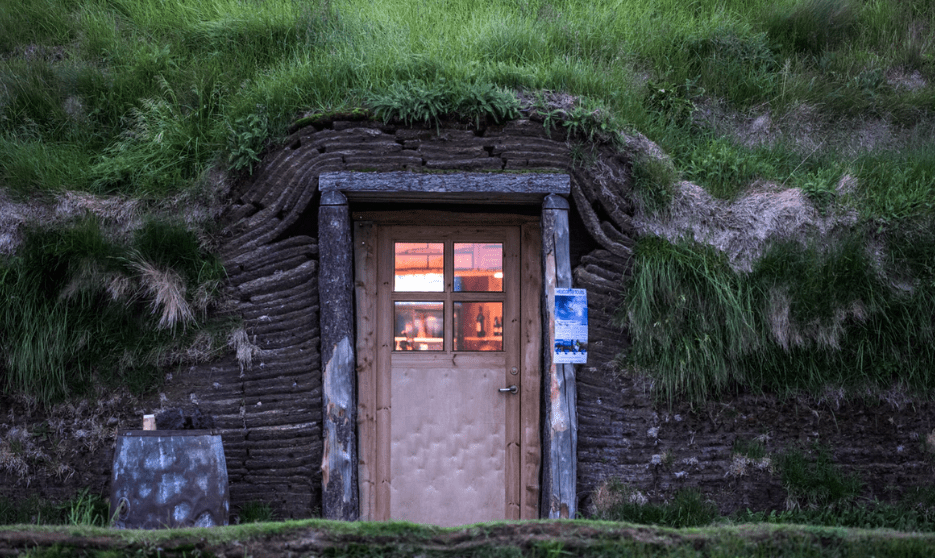 home or cottage in ground with wooden door