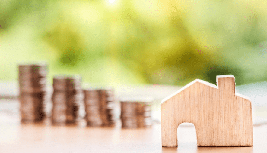 home investment illustrated with coins and wooden house figurine