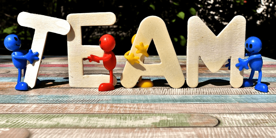 wooden letters spelling out team with figurines