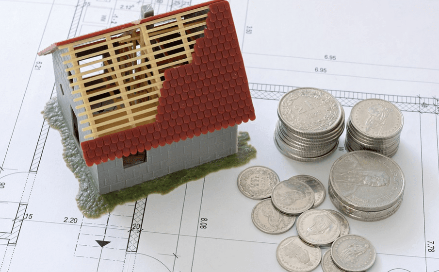 model of a damaged house and coins next to it