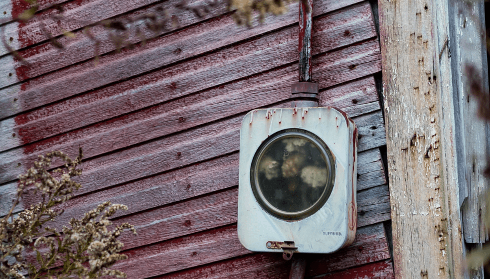 An old electric meter against an old building