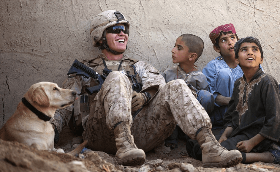 A soldier laughing with children