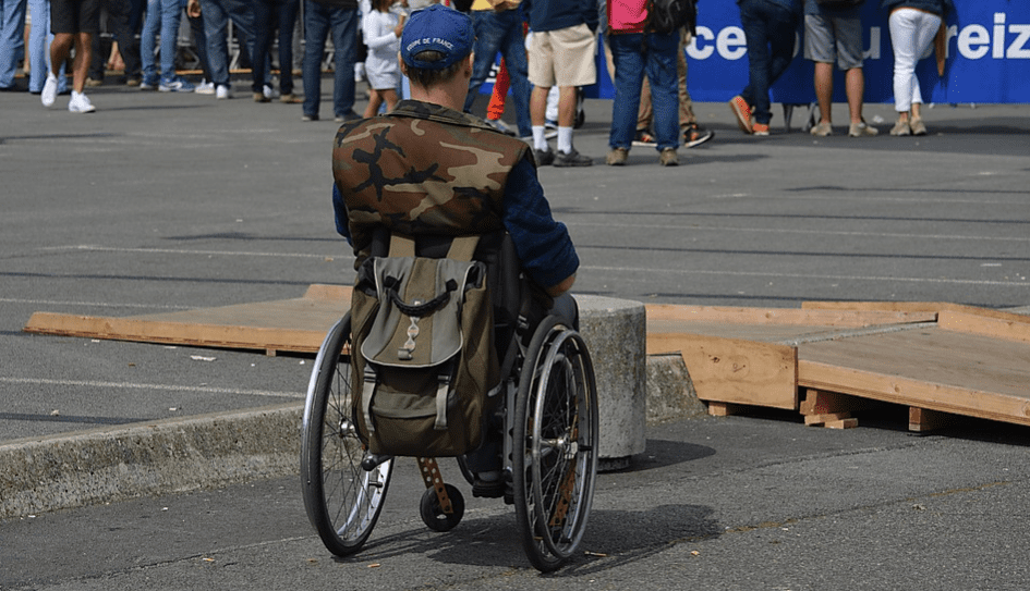 Man sitting in a wheelchair with camouflage vest