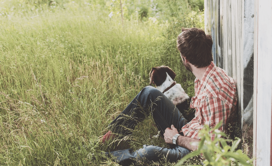A bachelor man sitting outdoors with his dog