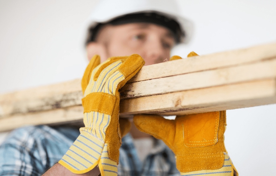 A construction worker carrying wooden beams