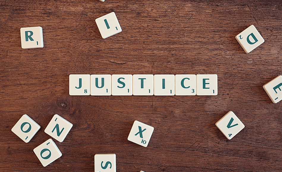 Scrabble tiles spelling out the word JUSTICE