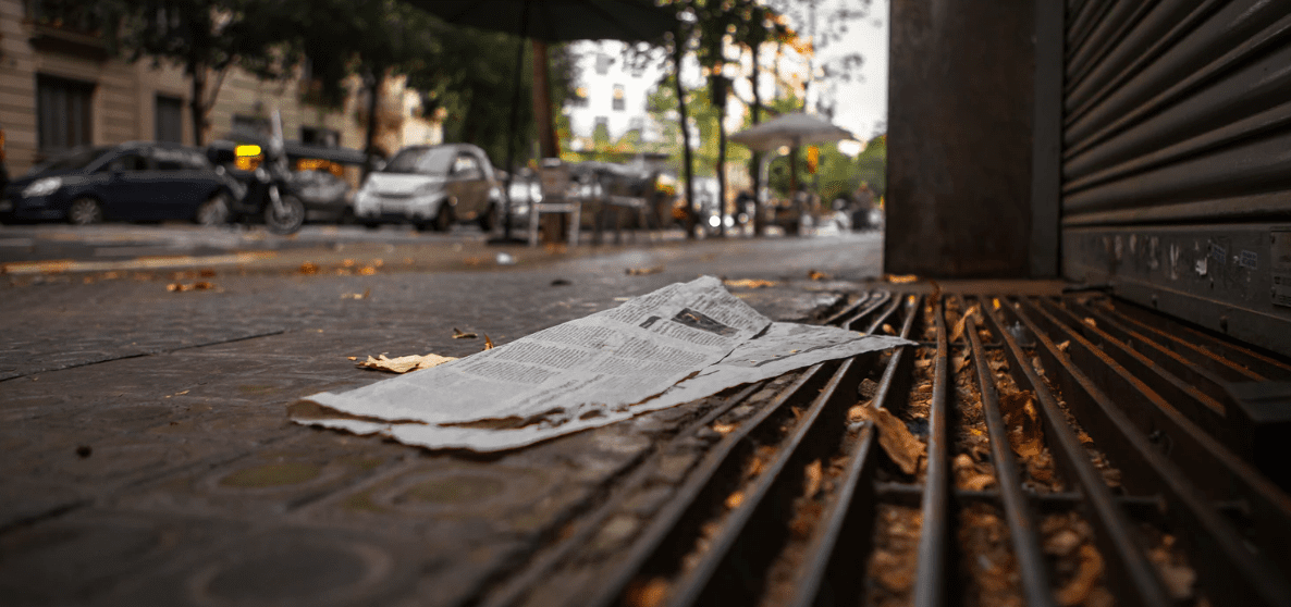 Newspaper on the ground of a sidewalk