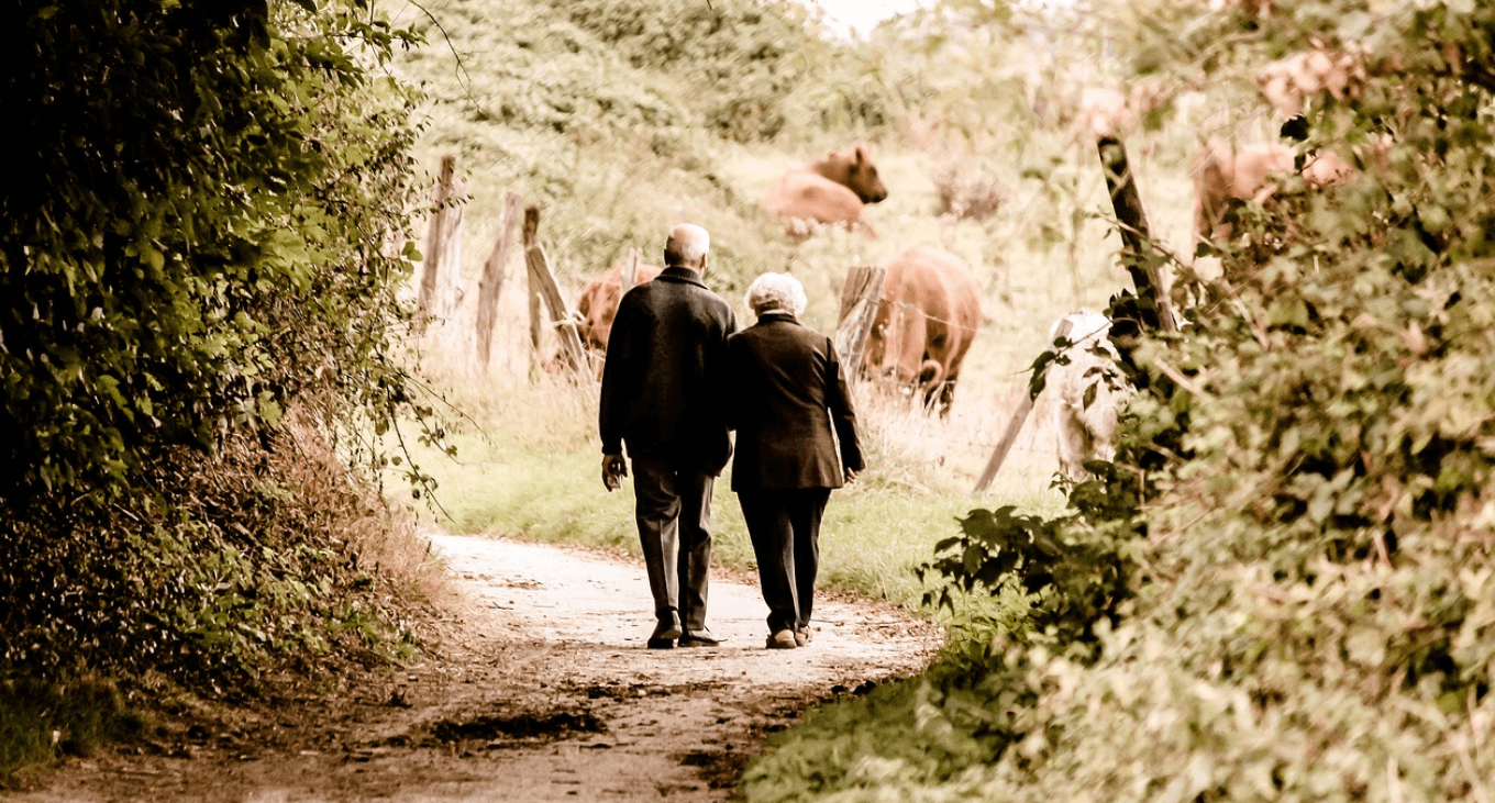 Senior couple walking down a lane