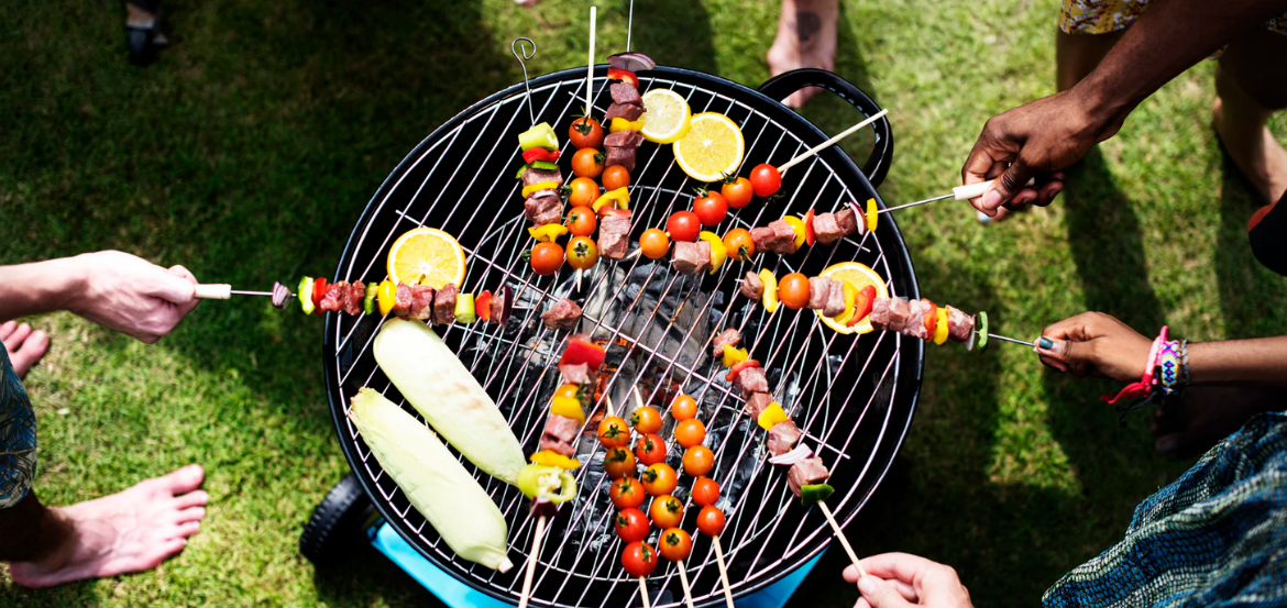 A group of people at a bbq party grilling skewers
