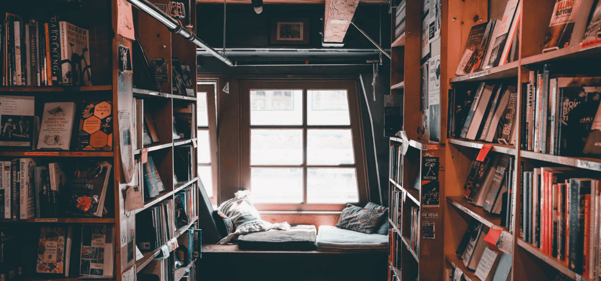Shelves of books in a library with a cozy nook and windows