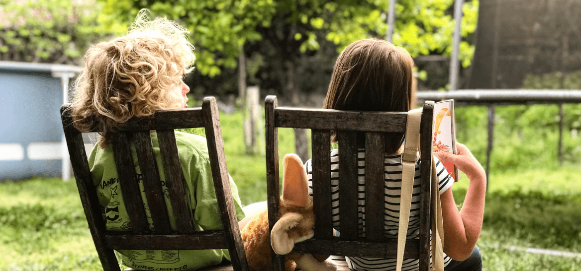A boy and a girl sitting on wooden chairs reading a book