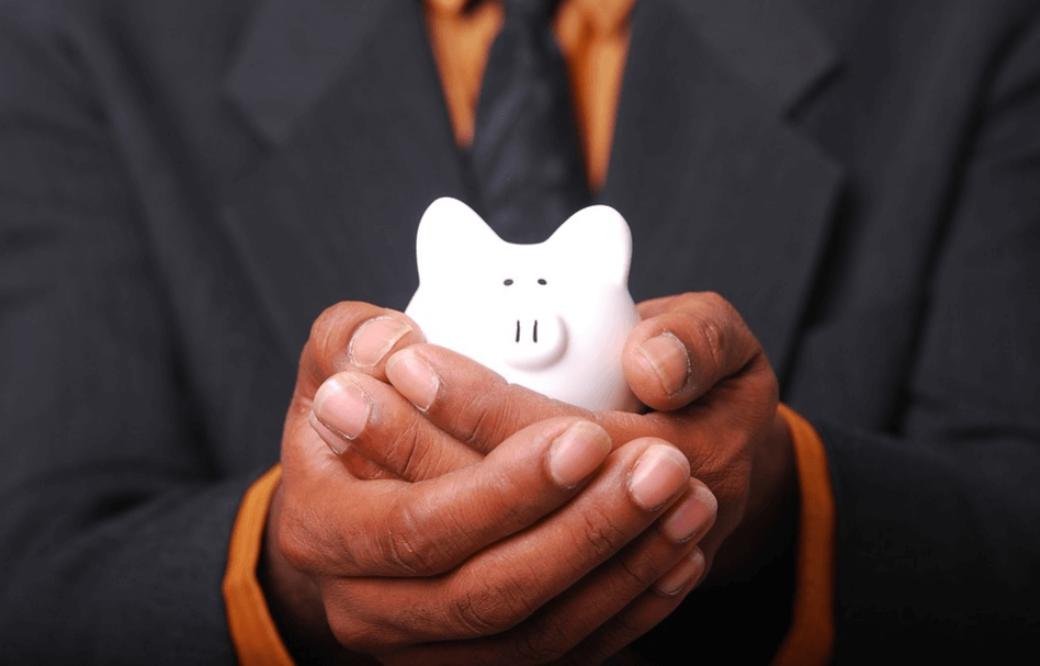 A man holding a small piggy bank in his hands