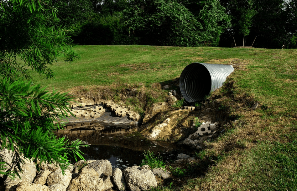 Sewer drain into a puddle
