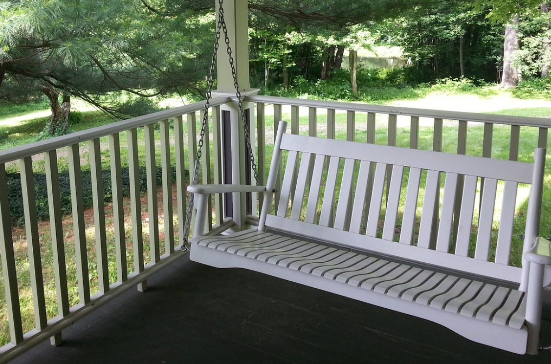 White porch swing on a deck