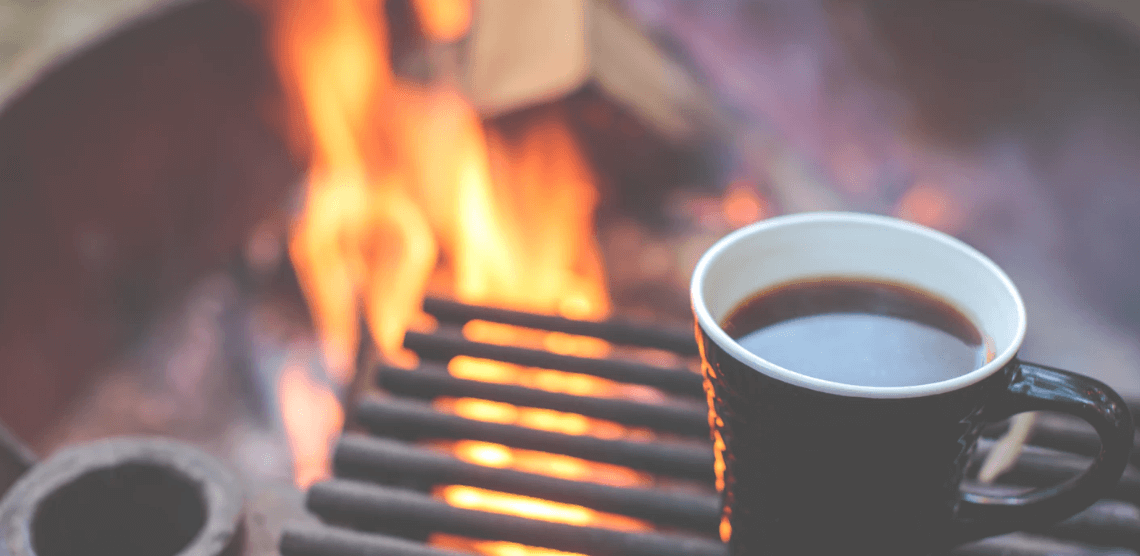 Coffee brewing in a mug over a firepit