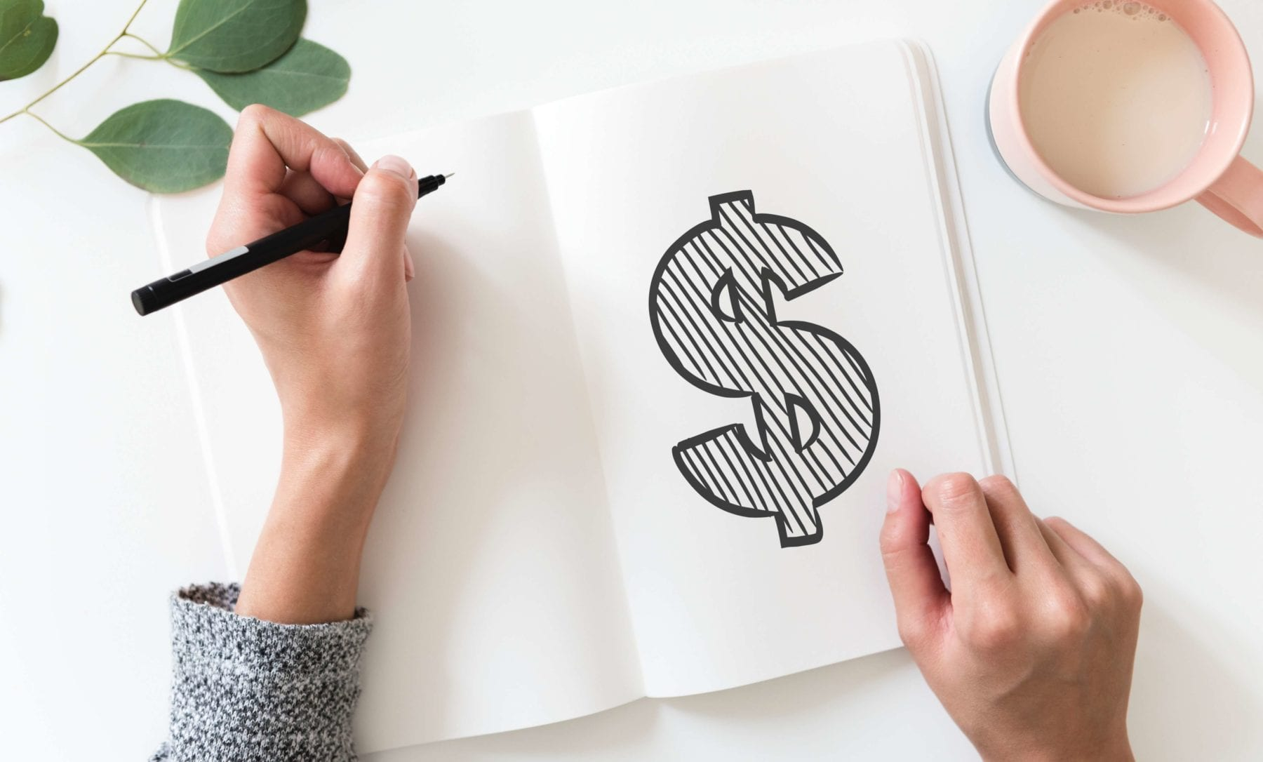 Woman drawing money sign in notebook - Photo by rawpixel on Unsplash