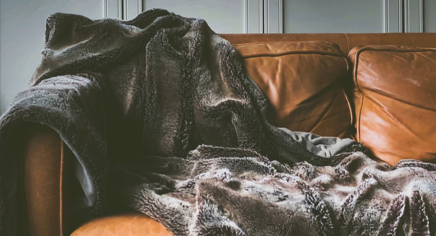 Soft blanket on a brown leather couch