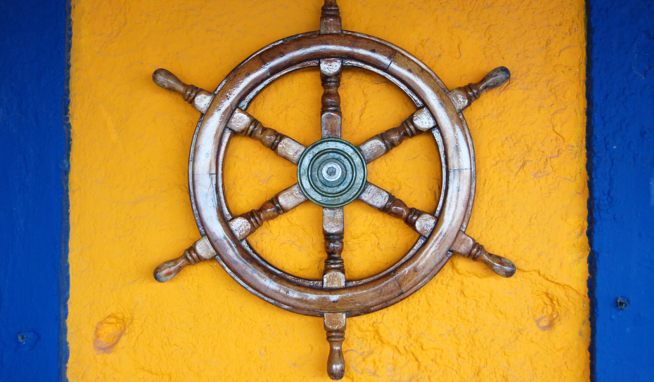 A ship's wheel hanging on the wall