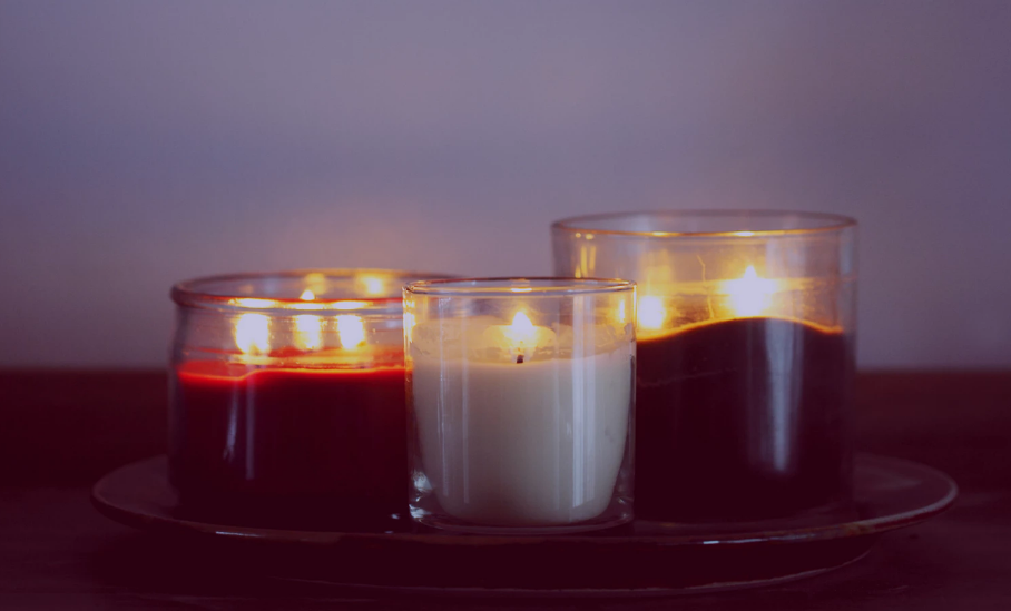 Three lit candles in jars