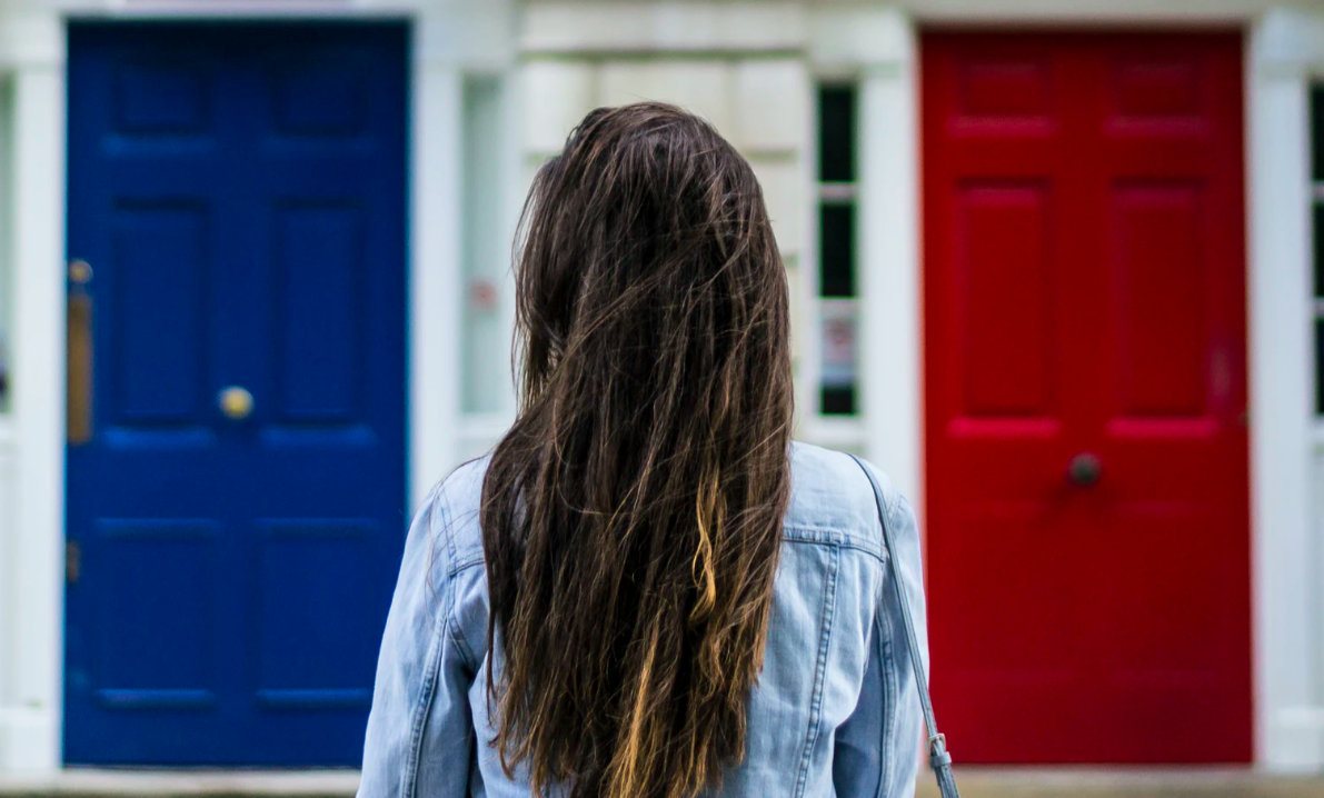 A woman standing in front of two house doors