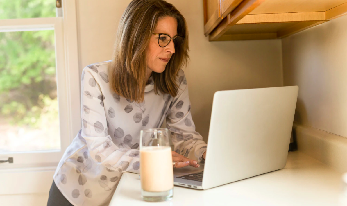 A woman with glasses typing on a laptop