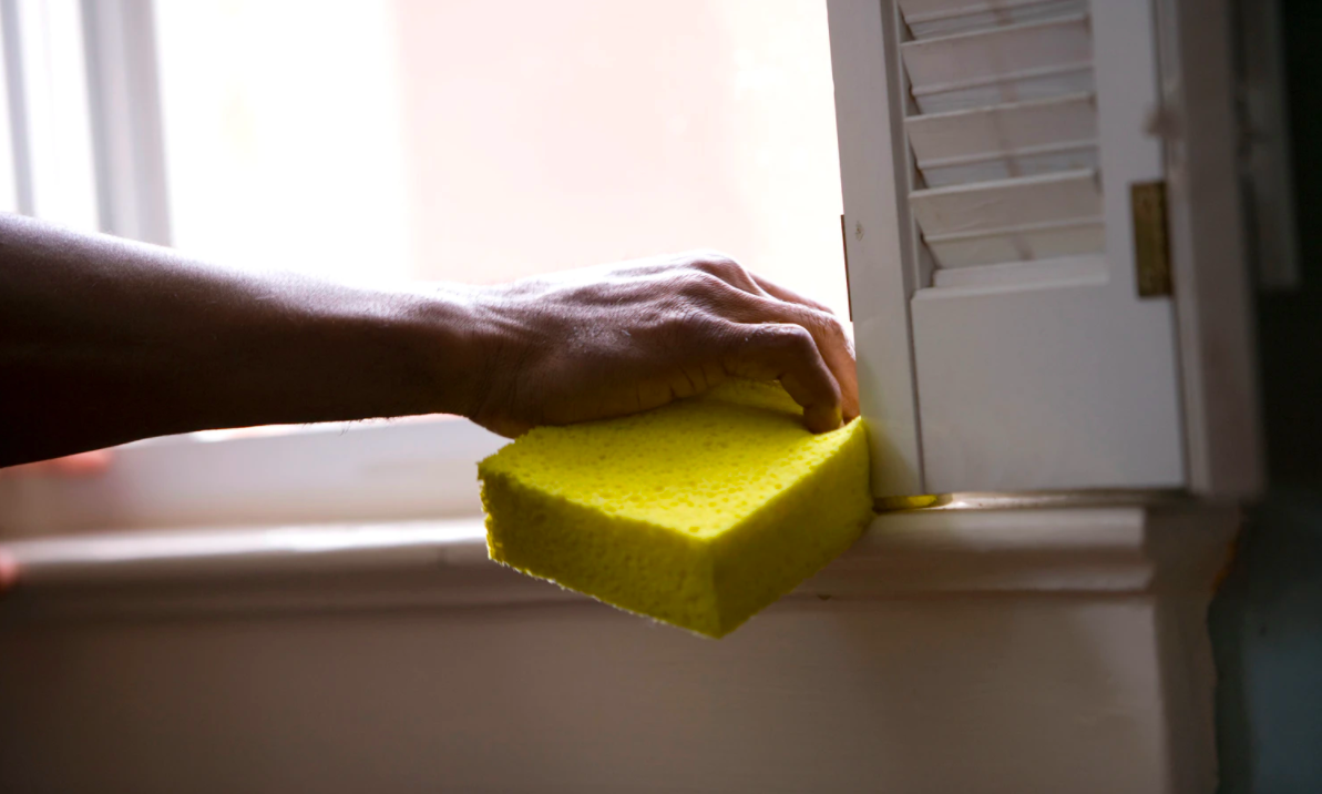 Person cleaning with a yellow sponge