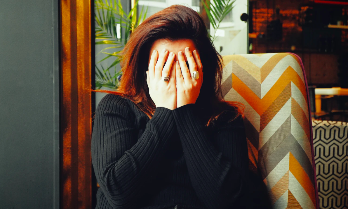 A woman covering her eyes with her hands