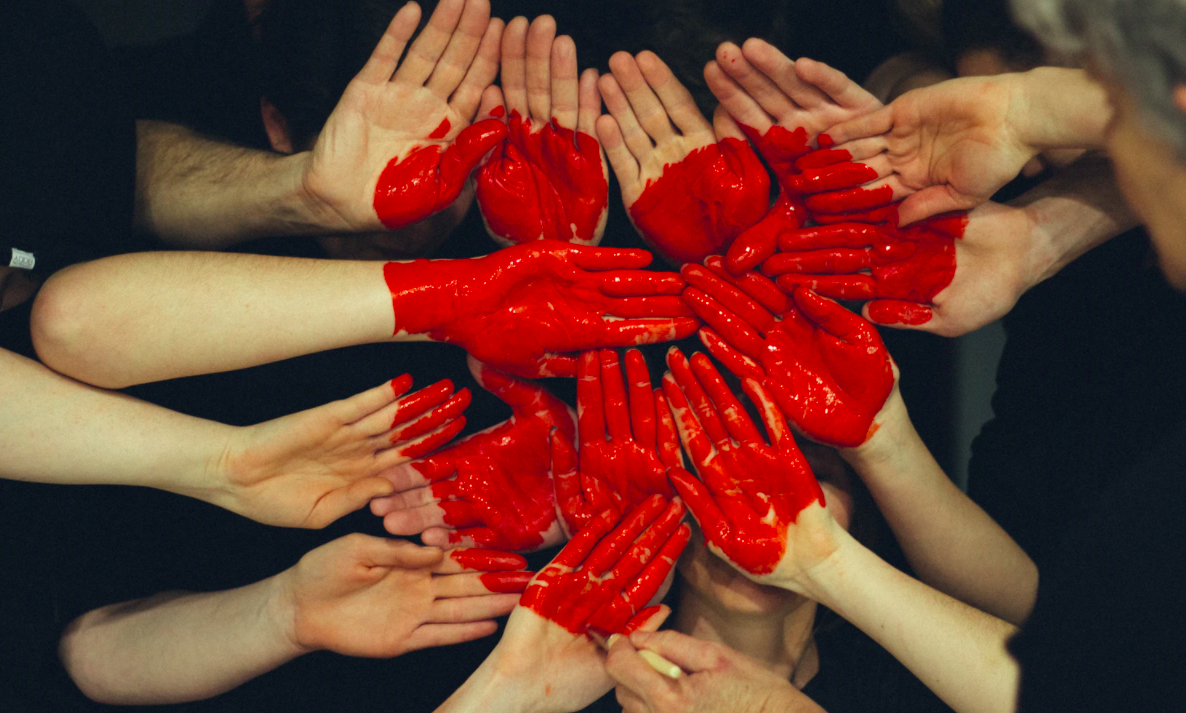 Hands painted together for a red heart